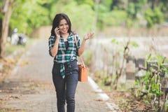 年轻亚裔妇女说在电话里,当走在同水准时 免版税库存照片