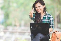 使用膝上型计算机的年轻亚裔妇女,当坐公园时 库存照片