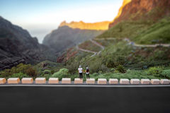 Ξένοιαστο ζεύγος που στέκεται στην άκρη του δρόμου βουνών Στοκ εικόνες με δικαίωμα ελεύθερης χρήσης