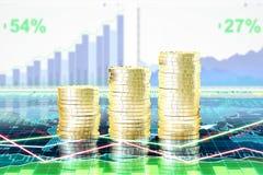 Кучи золотых монеток на экране с диаграммой дела на деле Стоковое Изображение