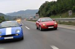 二赛跑在高速公路的跑车 免版税库存照片