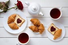 为夫妇用早餐在情人节用多士、心形的果酱、新月形面包、红色玫瑰花和茶,白色木 免版税库存图片