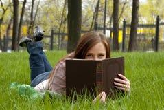 掩藏在书后的美丽的红头发人妇女 免版税库存照片
