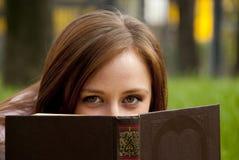 掩藏在书后的美丽的红头发人妇女 免版税库存图片