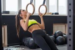 适合的与体操圆环的妇女去的引体向上在健身房 库存图片