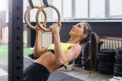 适合的与体操圆环的妇女去的引体向上在健身房 免版税图库摄影