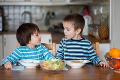 两个甜孩子,男孩兄弟,有为午餐意粉在 免版税库存图片