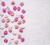 不同的颜色纸玫瑰堆积了白色木背景,情人节 免版税库存图片