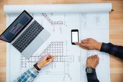 工作为图纸的两个人使用手机和膝上型计算机 库存图片