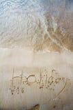 在沙子写的假日在海滩 免版税图库摄影