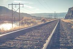 风景铁路在晴天有山和蓝天背景 -葡萄酒 免版税库存照片