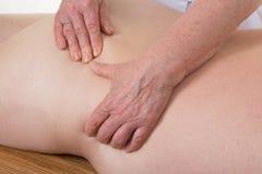 得到按摩治疗的人画象从女性手 免版税库存图片