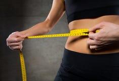 关闭妇女测量的腰部由在健身房的磁带 免版税库存图片