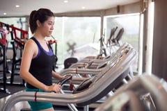炫耀跑在健身健身房的踏车的妇女年轻人 图库摄影