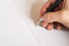 人的手候宰栏和文字某事在笔记本 免版税库存照片