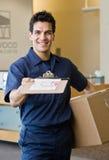 работник доставляющий покупки на дом представляя перевозку груза получения Стоковое Изображение RF
