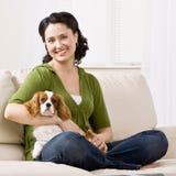 长沙发膝部小狗坐的妇女 免版税库存图片