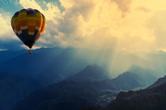 飞行在与光束的山的五颜六色的热气球 免版税图库摄影