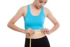 测量她的腰部的美丽的亚裔健康女孩 免版税库存照片