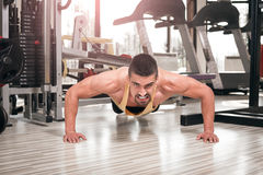 做在健身房的年轻人俯卧撑 图库摄影
