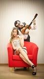 书呆子人男朋友戏剧尤克里里琴他的女朋友的爱情歌曲为情人节 免版税库存图片
