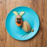 滑稽的野兔由土豆制成在板材 库存图片