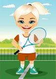有球拍的年轻在网球场微笑的小女孩和球 免版税库存图片