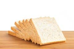 在白色背景中隔绝的木桌上的切片上添面包 图库摄影