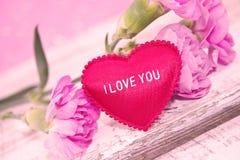 桃红色康乃馨开花与在土气白色木桌上的心脏 免版税库存照片