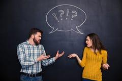 不快乐的夫妇争吵在黑板背景 免版税库存照片