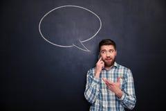 供以人员谈话在黑板的手机有讲话泡影的 免版税库存图片