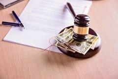 在木桌上的评断旁边判断惊堂木和金钱 免版税库存图片