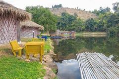 在湖附近的竹村庄房子,竹木筏和山 免版税图库摄影
