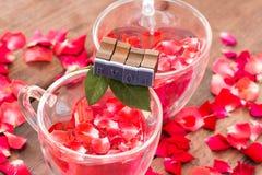 华伦泰、红潮在心脏杯子和爱消息的玫瑰 免版税库存图片