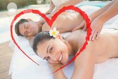 享受夫妇的有吸引力的夫妇的综合图象按摩游泳池边 免版税库存图片