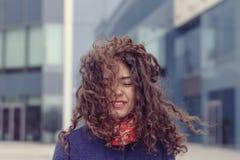 走在街道和风上的女孩弄糟了她的头发 免版税库存照片