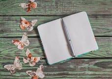打开干净的笔记薄和自创纸蝴蝶在木葡萄酒背景 顶视图,文本的自由空间 免版税库存图片