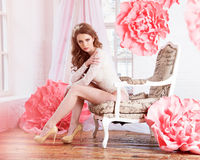 Όμορφο προκλητικό κορίτσι σε ένα μακρύ φόρεμα με τα τεράστια ρόδινα λουλούδια που κάθονται από το παράθυρο Στοκ φωτογραφίες με δικαίωμα ελεύθερης χρήσης