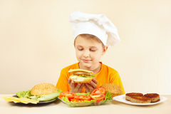 Маленький усмехаясь мальчик в шляпе шеф-поваров подготавливая гамбургер Стоковые Фотографии RF