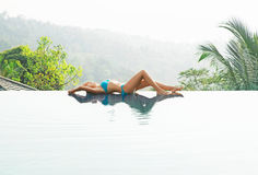 可爱,少妇在深蓝泳装说谎的游泳池边 免版税图库摄影