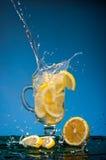 柠檬切落入一杯柠檬水和在蓝色背景的大飞溅 免版税库存图片