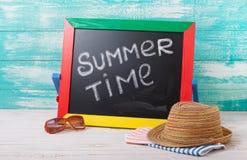 有文本的黑板它是夏时,辅助部件太阳镜,帽子,在木甲板的毛巾 库存图片