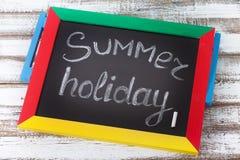 有文本的黑板它是夏时,辅助部件太阳镜,帽子,在木甲板的毛巾 免版税库存照片