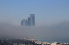 在雾围拢的海岸的摩天大楼大厦 免版税库存照片
