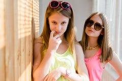 有两个美丽的白肤金发的十几岁的女孩乐趣愉快微笑 免版税库存图片