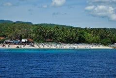 在一个海滩的传统木渔船与绿色棕榈和大海 免版税库存照片