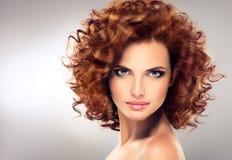 Довольно красная с волосами девушка с скручиваемостями Стоковое Изображение RF