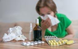 在得流感或寒冷的不适的妇女前面的药片 免版税库存图片