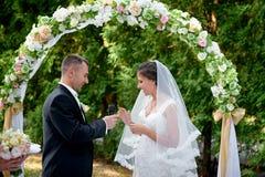 新娘新郎穿戴在手指的一个圆环在婚礼 免版税库存照片