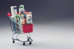 Вагонетка покупок вполне денег евро - банкнот - валюта Символический пример тратить деньги в магазинах, или выгодное приобретение Стоковые Изображения